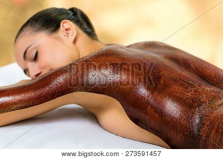 Close Up Detail Of Young Woman With Dark Chocolate Massage Wax Applied On Back. Girl Laying With Eye