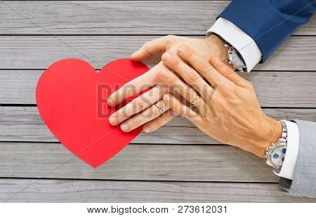 homosexuality, same-sex marriage, valentines day and love concept - close up of happy married male gay couple hands with red paper heart shape on table