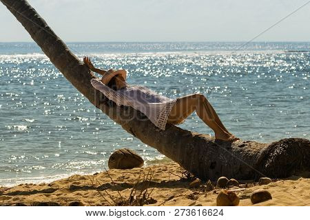 Beautiful Woman Relaxing On Palm Tree On The Beach. Healthy People Lifestyle. Woman Relaxing On The