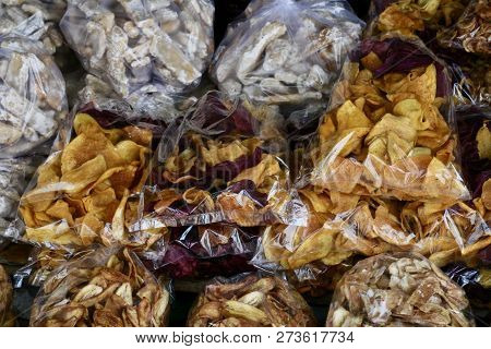 Bags Of Golden And Purple Sweet Potato Chips, Sugar Coated Treats And Banana Chips Sold As Street Fo