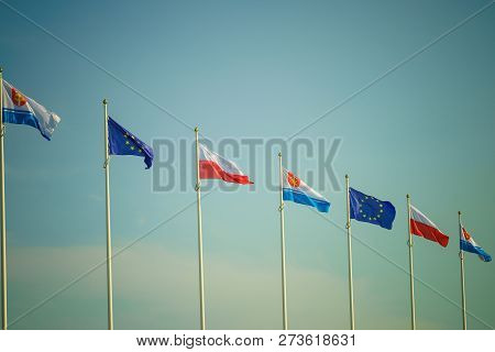 Flags Against Sky In The Wind. Flag Of Poland, The Flag Of European Union And The Flag Of Polish Cit