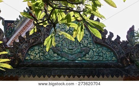 Green Demon Carved Into A Temple Facade In Asia With Sunlit Leaves