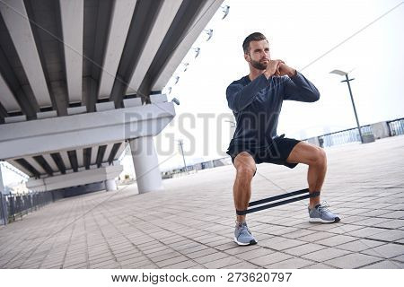 Young Sporty Man Doing Exercises With Rubber Band Outdoor.