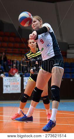 KAPOSVAR, HUNGARY – DECEMBER 2, 2018: Ildiko Szivos (with ball) in action at a Hungarian National Championship volleyball game between Kaposvar (white) and Palota VSN (blue) in Sportcsarnok Kaposvar.