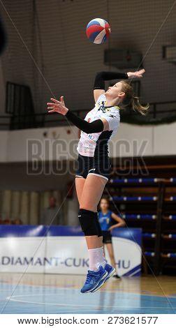 KAPOSVAR, HUNGARY – DECEMBER 2, 2018: Ildiko Szivos serves ball at a Hungarian National Championship volleyball game between Kaposvar (white) and Palota VSN (blue) in Sportcsarnok Kaposvar.