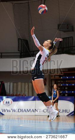 KAPOSVAR, HUNGARY – DECEMBER 2, 2018: Zsofia Harmath serves ball at a Hungarian National Championship volleyball game between Kaposvar (white) and Palota VSN (blue) in Sportcsarnok Kaposvar.