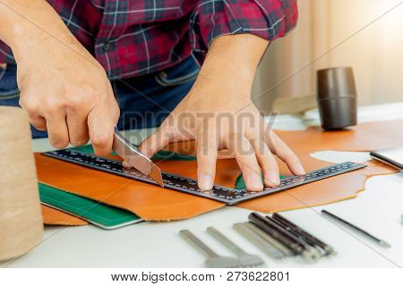 Leather craftsman with red shirt working measuring and cutting on genuine leather, Handcraft handmade concept. poster