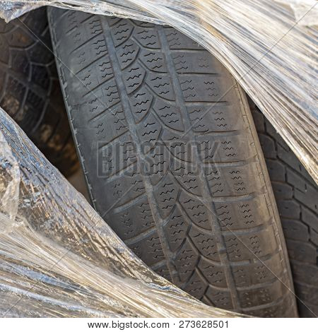 Worn Out Tires Of Heavy Vehicles Wrapped In Plastic