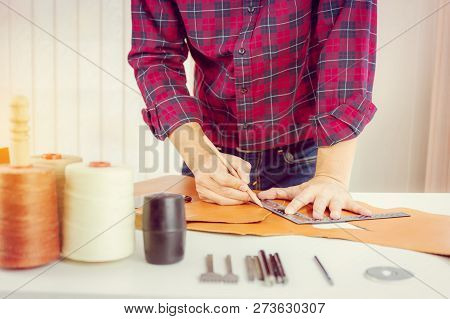 Leather craftsman with red shirt working measuring and writing on genuine leather, Handcraft handmade concept. poster