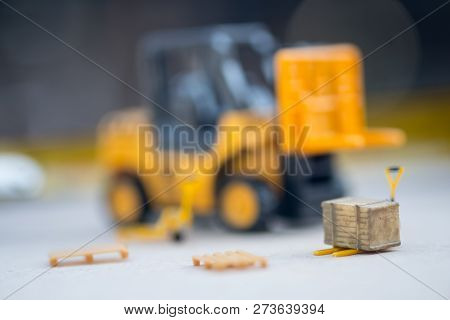 Miniature Yellow Toy Forklift And Miniature Pallet Truck. Concept Of International Freight Transport