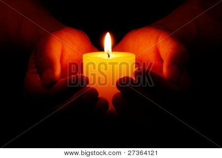 Heart-shaped hands holding yellow candle in dark