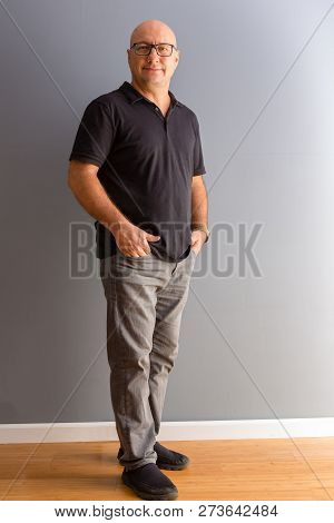 Full Length Portrait Of Adult Middle-aged Bold Man In Glasses, Wearing Black Polo And Grey Jeans, St
