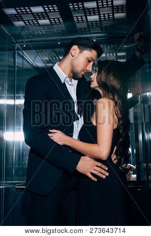 Beautiful Romantic Couple Passionately Looking At Each Other And Embracing In Elevator