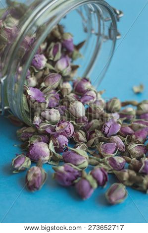Dried Rose Flowers In A Glass Jar. Herbal Tea On Blue Background, Vertical Photo
