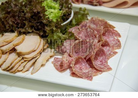 A Salami Sausage Slice And Vegetables On Plate