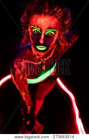 Portrait Of A Beautiful Young Sexy Girl With Ultraviolet Paint On Her Body. Pretty Woman With Glowin