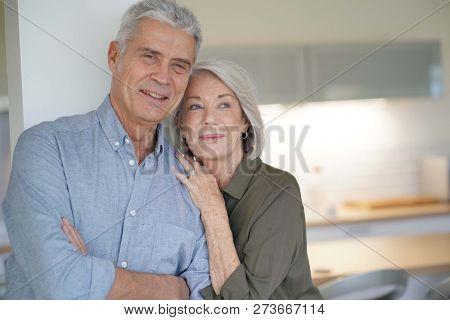 Loving portrait of happy senior couple at home