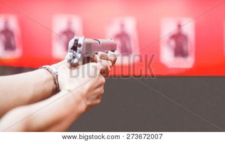 Woman Both Hands Holding Magnum Gun, Index Finger On Trigger, Aiming Ready To Shoot On Targets On Re