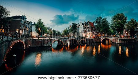 Evening Twilight Panorama Of Amterdam Cityscape With Canal, Bridge And Medieval Houses In The Evenin