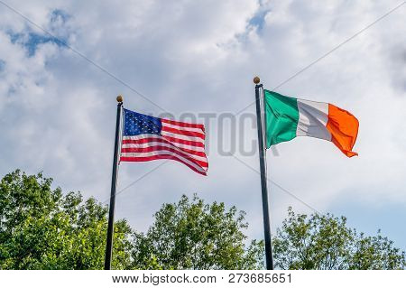 Flags Of United States And Irland Fluttering Against A Blue Sky, Near Rhode Island Irish Famine Memo