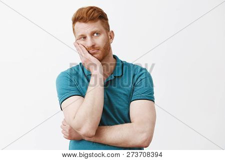 Waist-up Shot Of Bored And Tired Gloomy Redhead Guy With Bristle In Green Polo-shirt, Leaning Face O