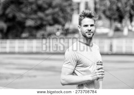 Staying hydrated. Man athletic appearance holds water bottle keep staying hydrated during training. Guy sport clothes refreshing. Athlete cares body hydration after training at stadium sunny day. poster