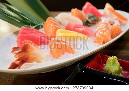 Mixed Sliced Fish Sashimi On Ice In White Bowl. Sashimi Salmon Tuna Hamachi Prawn And Surf Calm Set,