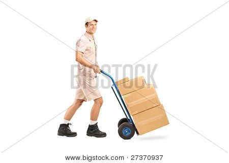 Full length portrait of a delivery boy pushing a handtruck isolated on white background