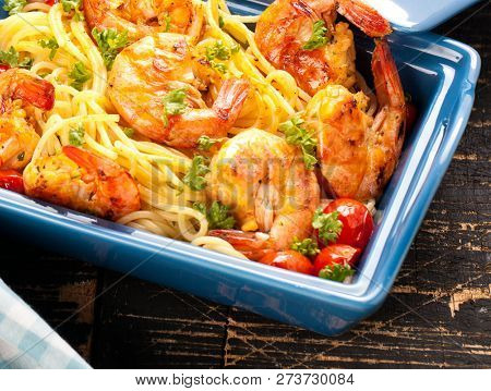 Stir-fried spaghetti with grilled shrimps and tomatoes - Italian fusion food style. poster