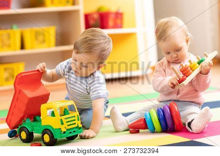Kids Playing With Educational Toys. Children Sit On A Rug In A Play Room At Home Or Kindergarten. To