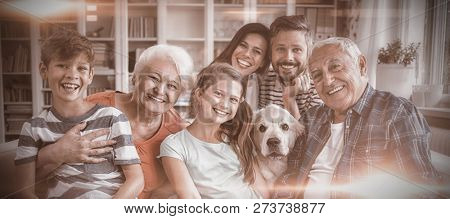 Portrait of happy multi generation family sitting on sofa in living room at home