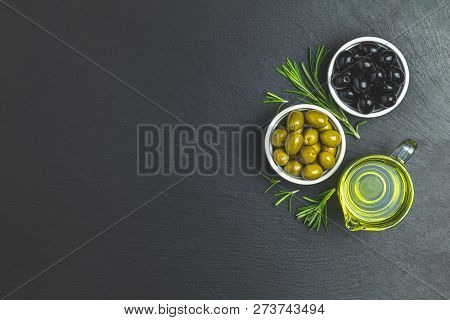 Set Of Black And Green Olives On Plates, Olive Oil And Rosemary On A Black Stone Background. Top Vie