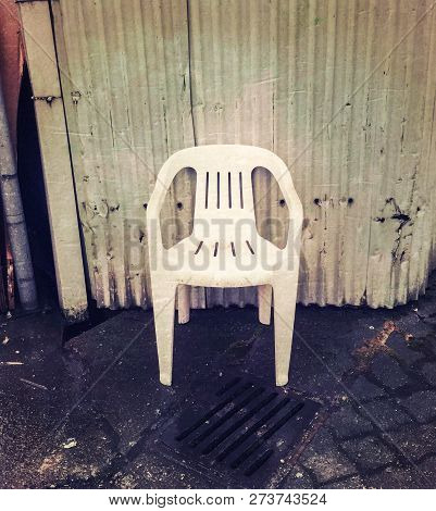 Empty Cheap White Plastic Chair In Grungy Alleyway.