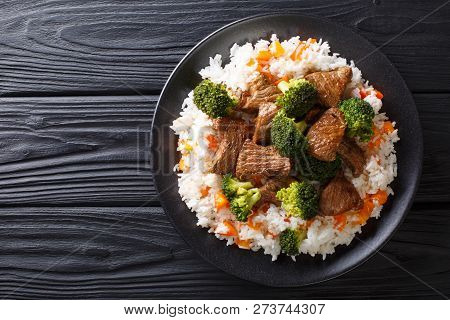 Portion Of Fried Beef With Broccoli With Rice Garnish And Persimmon Close-up On A Plate. Horizontal
