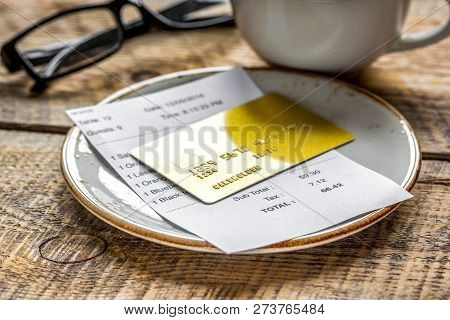 Coffee And Receipt Bill For Payment By Credit Card On Wooden Tab