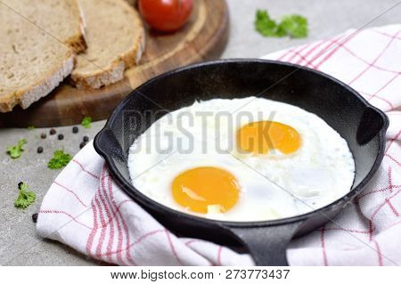 Delicious Fried Eggs In A Cast Iron Pan. Top View Of Eggs And Bread, Breakfast Scene.