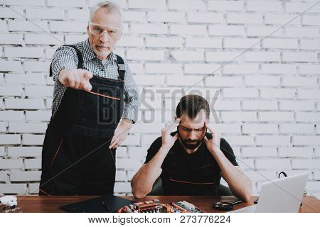 Angry Elderly Man Pointing Finger At Screen. Upset Young Man Sitting At Table. Young And Old Workers
