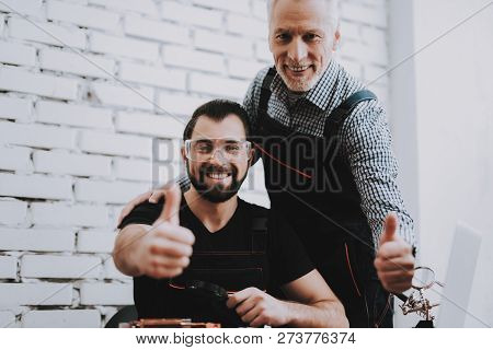 Two Exited Smiling Men In Uniform In Workshop. Repair Shop. Thumbs Up. Computer Hardware. Young And