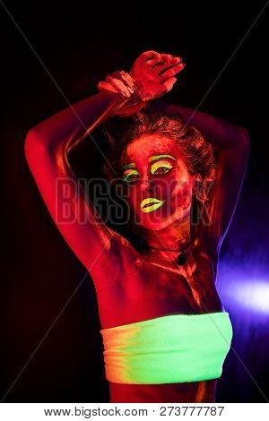 Portrait of a beautiful young sexy girl with ultraviolet paint on her body. Pretty woman with glowing bodyart in black lamp light poster