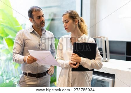 Young Female Trainee Explaining Spreadsheet Data To Boss. Mid Adult Bearded Executive Asking Young B