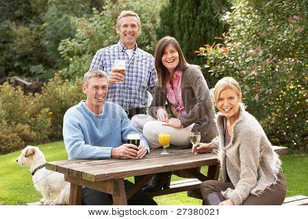 Group Of Friends Outdoors Enjoying Drink In Pub Garden