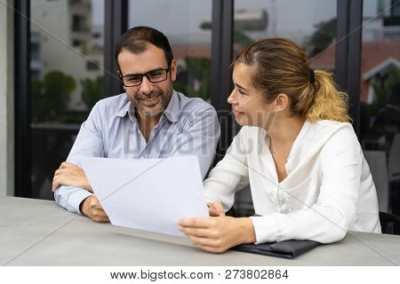 Positive Female Customer Showing Documents To Advisor. Male And Female Business Colleagues Reading R