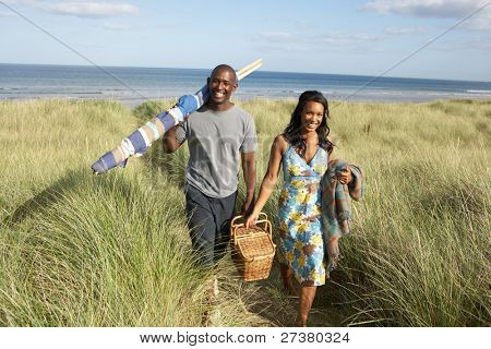 Young Couple Carrying Picnic Basket And Windbreak Walking Through Dunes poster