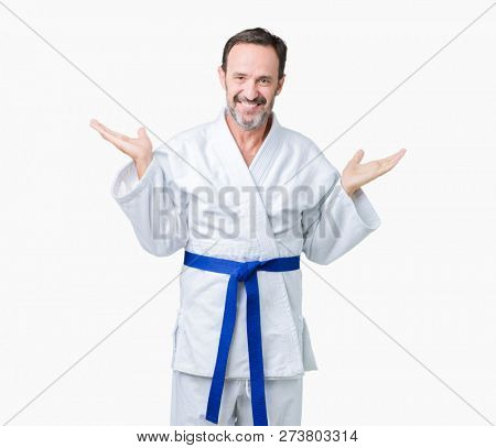 Handsome middle age senior man wearing kimono uniform over isolated background Smiling showing both hands open palms, presenting and advertising comparison and balance