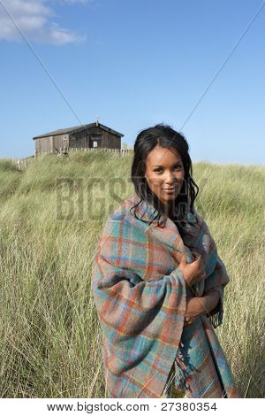 Young Woman Standing On Beach Wrapped In Blanket With Beach Hut In Distance