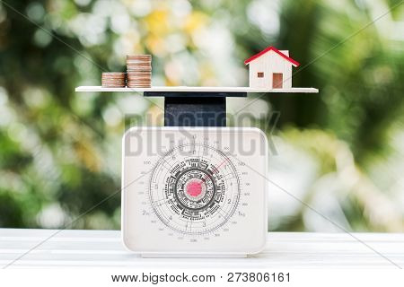 Home Money Coins On Balance Weighing Scales On Wood Green Background. Concept Of Saving Buy New Home