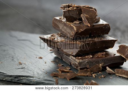 Melted Chocolate Pouring Into A Piece Of Chocolate Bars On A Table.