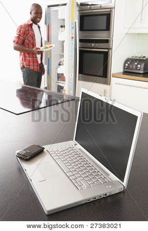 Young Man Fixing Snack In Kitchen With Laptop In Modern Kitchen