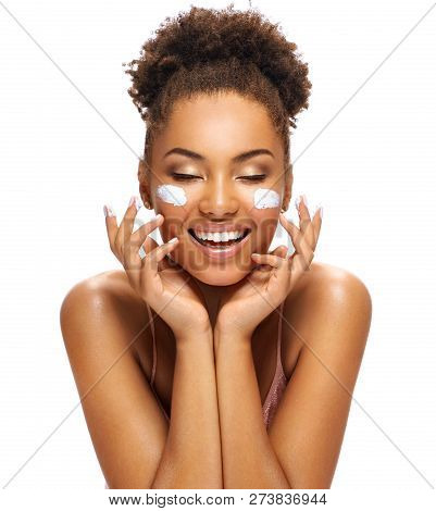 Happy Young Girl With Moisturizing Cream On Her Face. Photo Of Smiling African American Girl Isolate