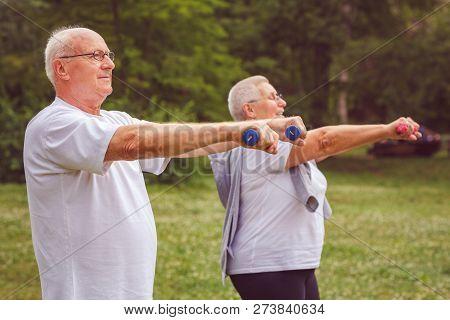 Senior Exercise - Elderly Man Exercising With Dumbbells In A Park
